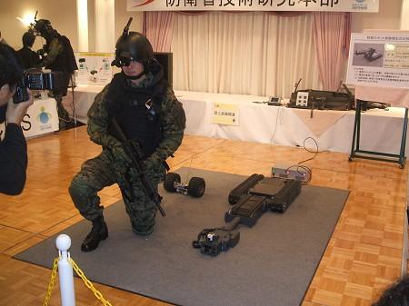 しゃがんだ姿勢で構える「先進個人装備」を装備する隊員。右側に転がっているのは「携帯型ロボット」(後述)