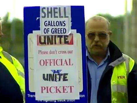 ピケットラインを形成するトラック運転手とプラカード。「SHELL GALLONS OF GREED(シェルはガソリン高騰に乗じた欲張りだ)」との文字が見える。
