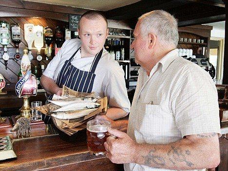 パブの料理長で店の経営者でもあるTim Abbott氏(左)と交渉中(?)のお客