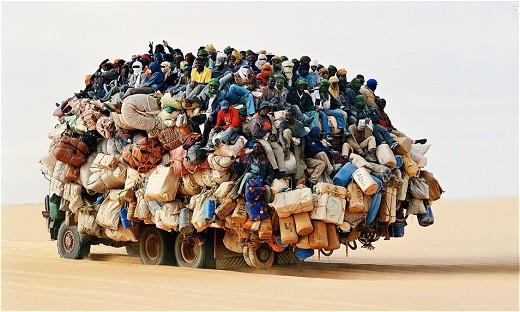 出稼ぎ労働者たちが乗り込むトラック……だと思われるが車自身のディテールすら分からないほどの乗車率