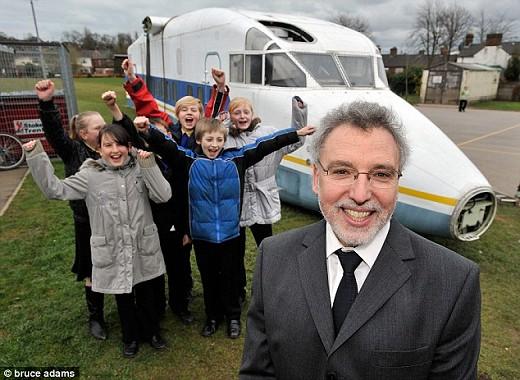 学校に運ばれる飛行機の胴体部分(上)と、「空飛ぶ教室」が到着して喜ぶ子どもたちと先生(下)