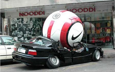 日本なら思わず110番通報したくなるようなシーン。巨大なサッカーボールが自動車を粉砕している。