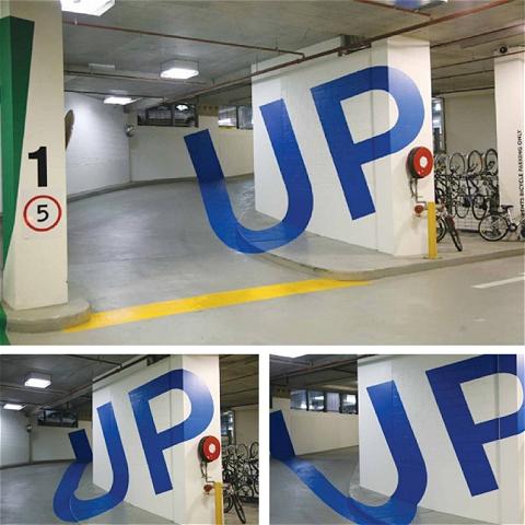 地下駐車場における「UP」(登り)を示す「歪み絵」。入口近くから見ると、「UP」の文字がキレイに浮かび上がって見える。