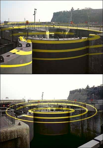 普通に見ると、警戒用のものだろうか、黄色の線が無造作に塗っているだけのように見えるが、ある視点から見るといくつにも重なった同心円が浮き出て見える