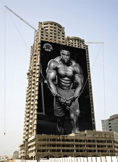 ケーブルフライをする男性。ビルの両脇のクレーンの固定用ケーブルをうまくポスターと連動させている。