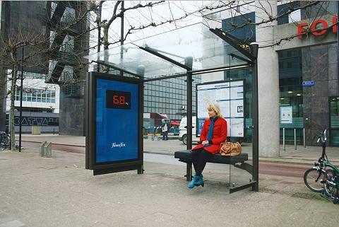 ご婦人が停留所の椅子に座るとあら不思議。彼女の体重がデジタル盤に。体重の一般公開をしてしまうという仕組み。