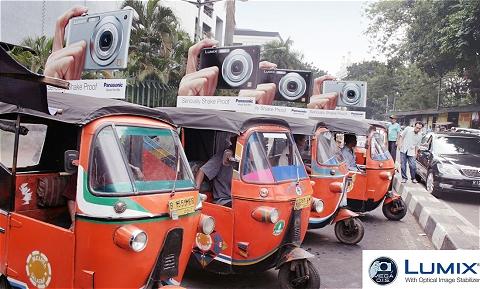 3輪タクシー「バジャイ」に撮り付けられた「Lumix」と、それを持つ人の手のプレート