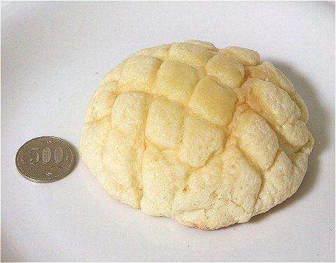 中身を取り出してみる(上)。さらに大きさを比較するため、メロンパンの横に五百円玉を置いてみる(下)。