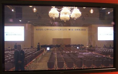 ↑ 設営中の会場内の様子。正面ステージ部分に経営陣が陣取ることになる。