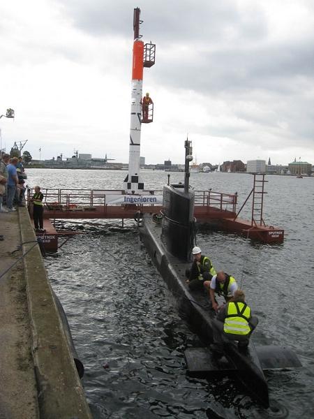 ↑ 湾岸で準備中のプラットフォーム・「HEAT-1X」・小型潜水艦「UC3 Nautilus」。上部の橙色の部分が小型有人宇宙船「ティコ・ブラーエ」