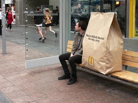 ↑ バスの停留所でバスを待つ男性。男性とマックの袋、どちらがバス待ちをしているのか分からなくなる