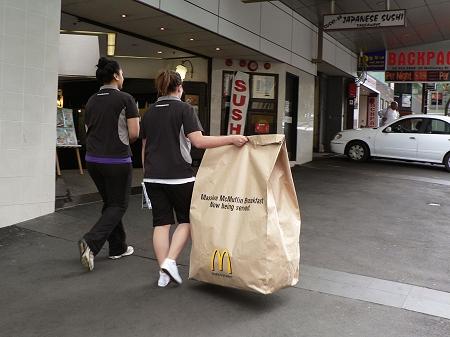 ↑ 街中をさっそうと歩く女性の手にも「マッシブマックマフィン」の袋。子供が後をつけて「でけぇよ!」というツッコミをしてきそう