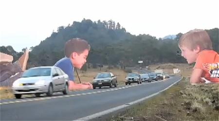↑ 公道を通り過ぎる自動車達の様子を楽しむかのように見える子供達の看板