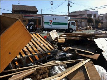 ↑ 未だ復旧が進まず破損した家屋の跡が残る周辺地域と、休業中の店舗、そして移動販売車