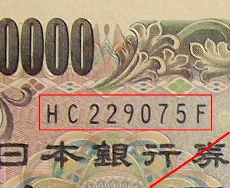 ↑ 現行一万円札の記号と番号。黒色だが、7月19日以降の発行分は褐色になる