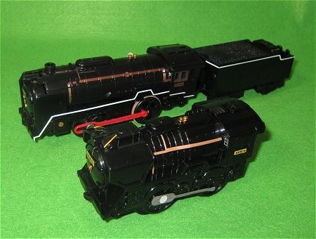 ↑ ハッピーセットのD51(手前)とプラレール本製品のC62(奥)を並べてみる。元々D51とC62では動輪数が違うので単純比較はできないが、動輪部分の簡略の切り口は同じ。ただし長さの縮め方は大幅に異なるし、ハッピーセット版では炭水車(石炭を運ぶ車両)が省略されている。