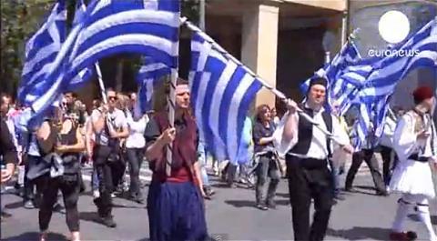 ↑ ギリシャの公務員削減に抗議するデモを伝える報道映像。