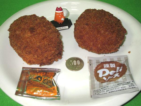 ↑ ゲンコツコロッケ(左)とゲンコツメンチ(右)。中央部分においたサイズ比較用の500円玉で、その大きさは分かるはず